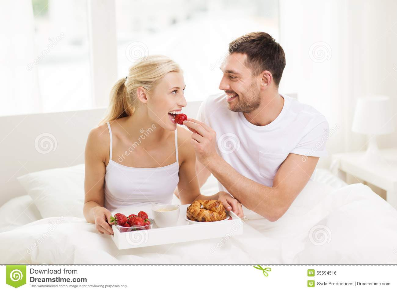 Happy couple having breakfast in bed at home stock photo for Lovers home