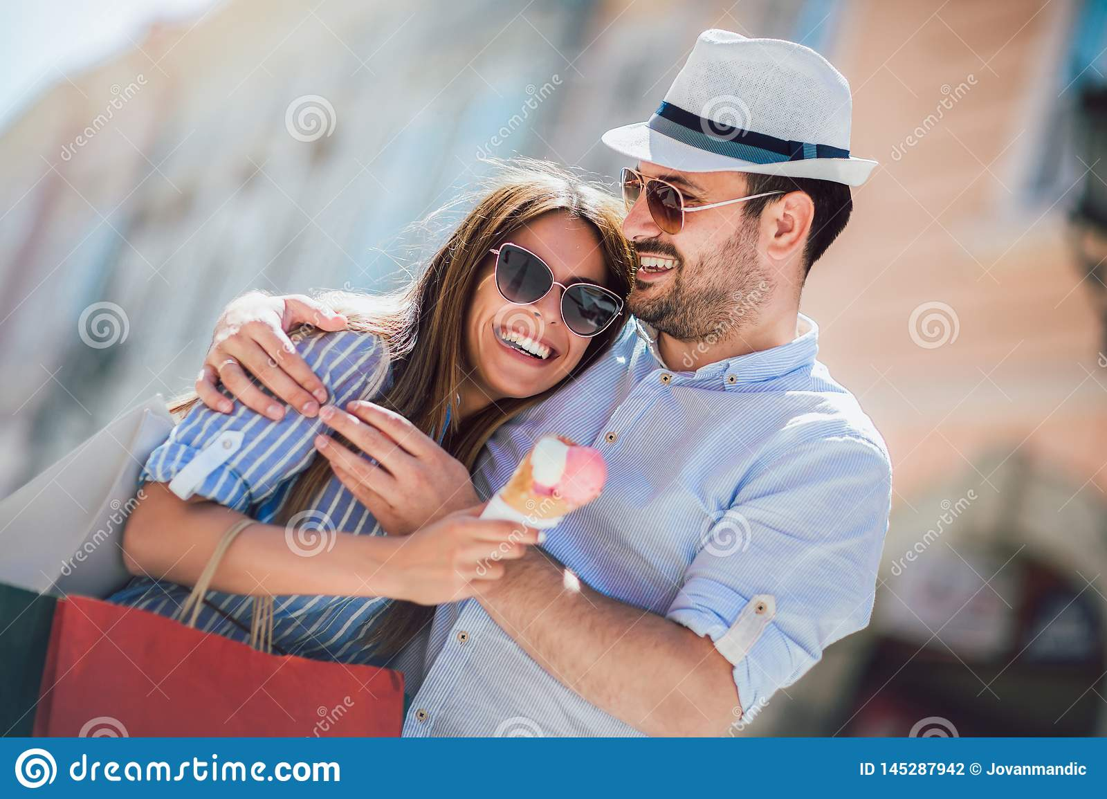 Couple having date and eating ice cream after shopping
