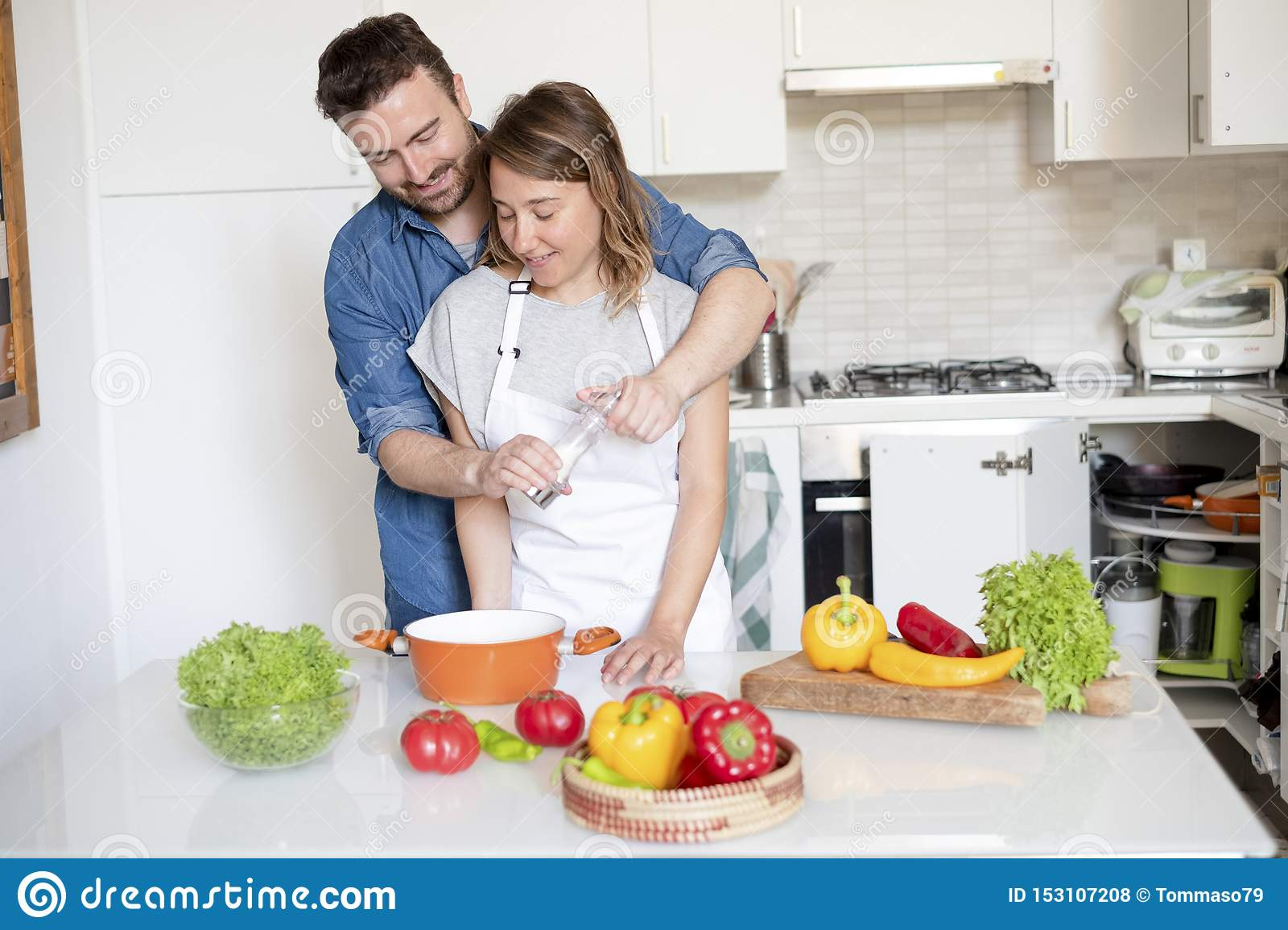Happy couple in home kitchen cooking together vegetables
