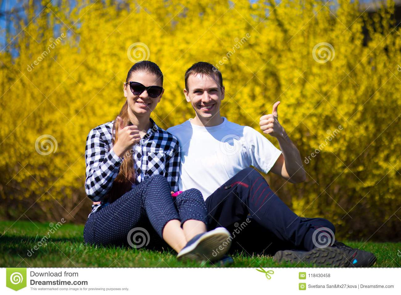 Happy couple hugging on fresh grass in park