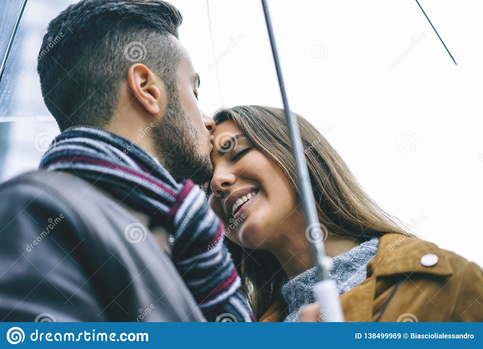 Happy couple kissing under an umbrella in a rainy day - Handsome man kiss his forehead girlfriend under the rain - Love, people,