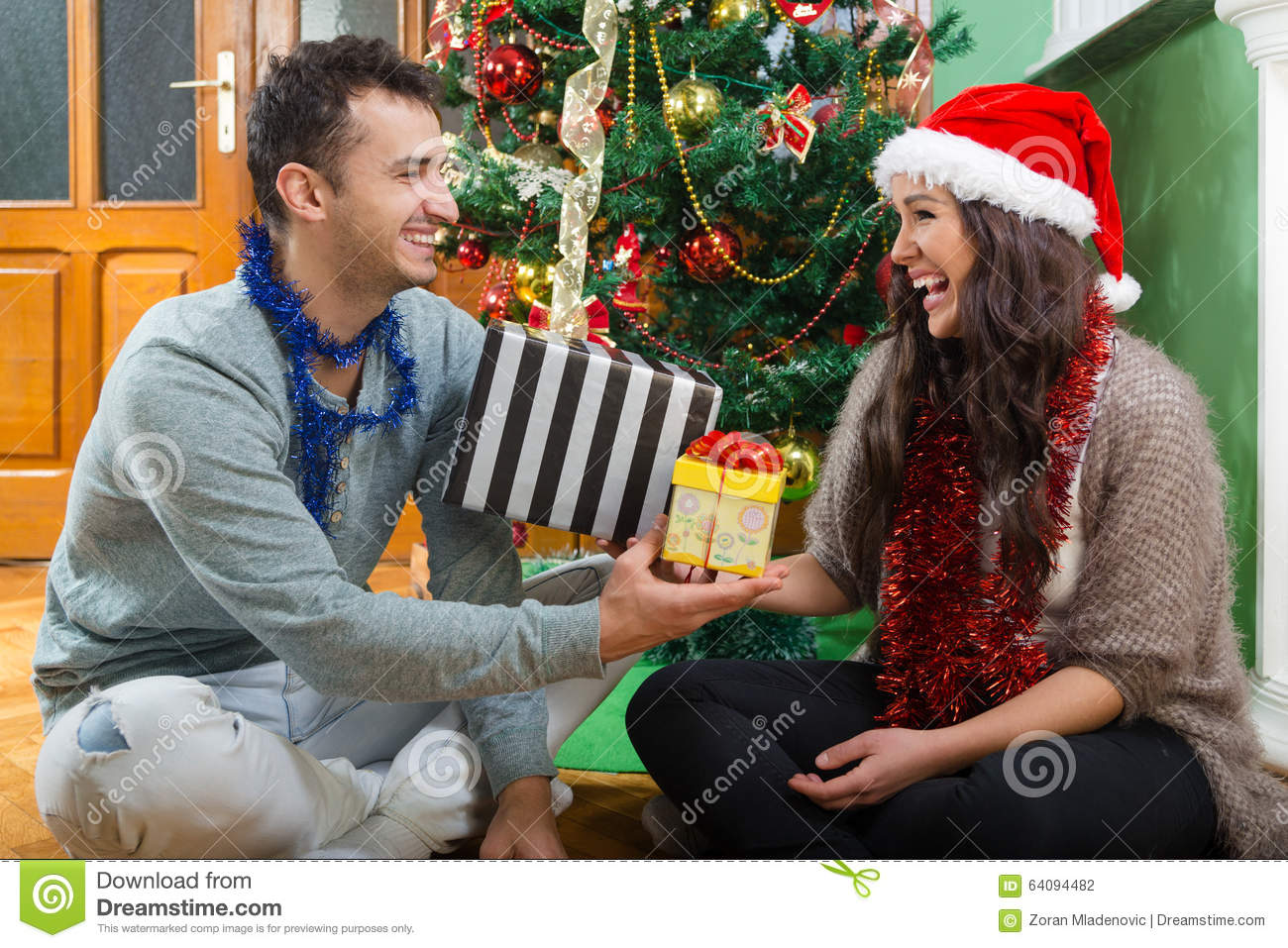 Happy couple laughing and enjoying Christmas presents
