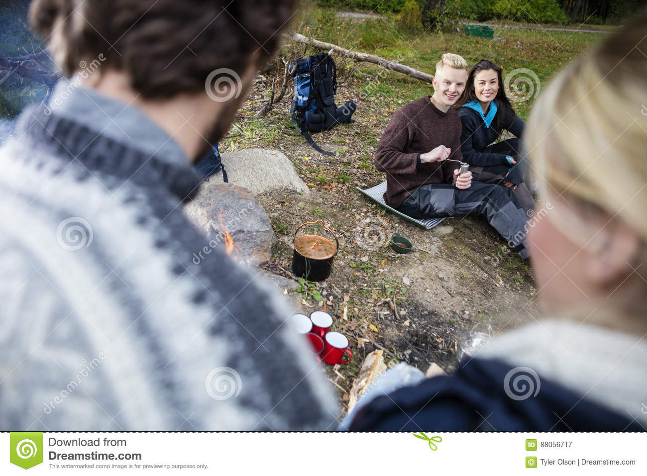 Happy Couple Looking At Friends During Camping