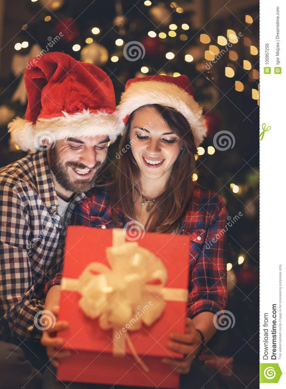 Happy couple looking gift in box at New years Eve