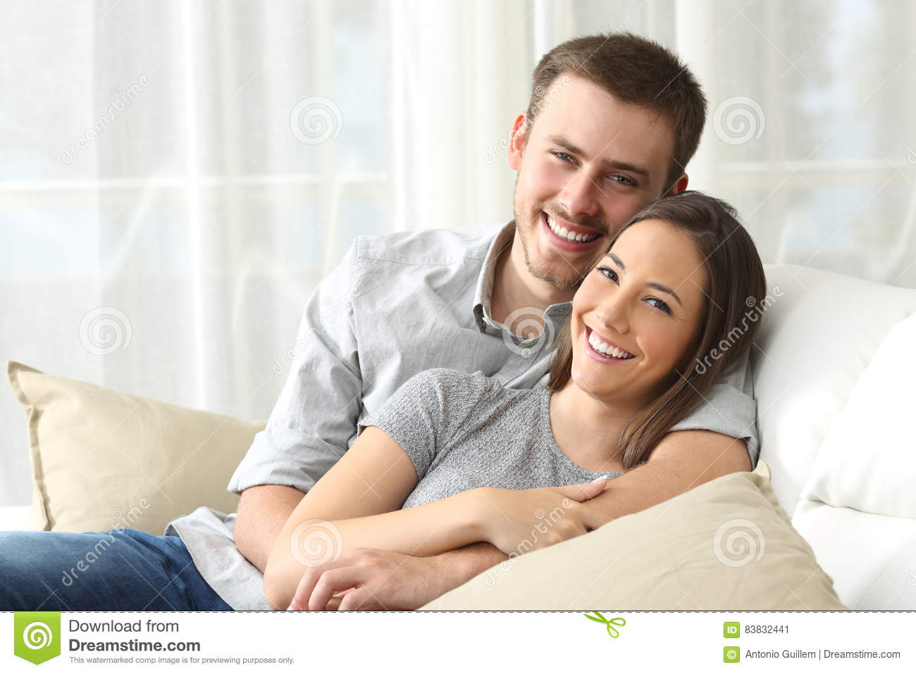 Happy couple looking to camera at home