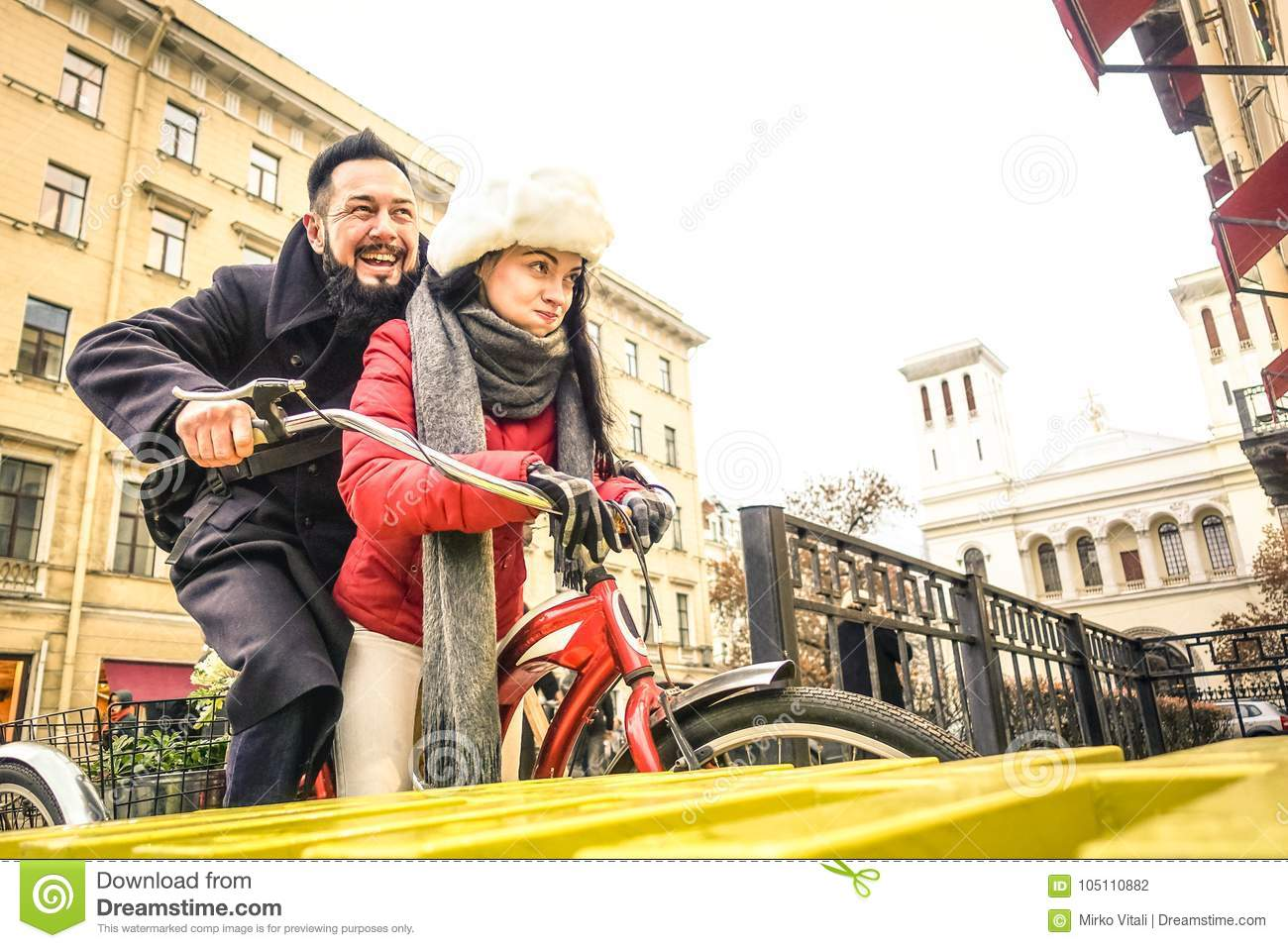 Happy couple in love enjoying winter time outdoor on vintage bicycle