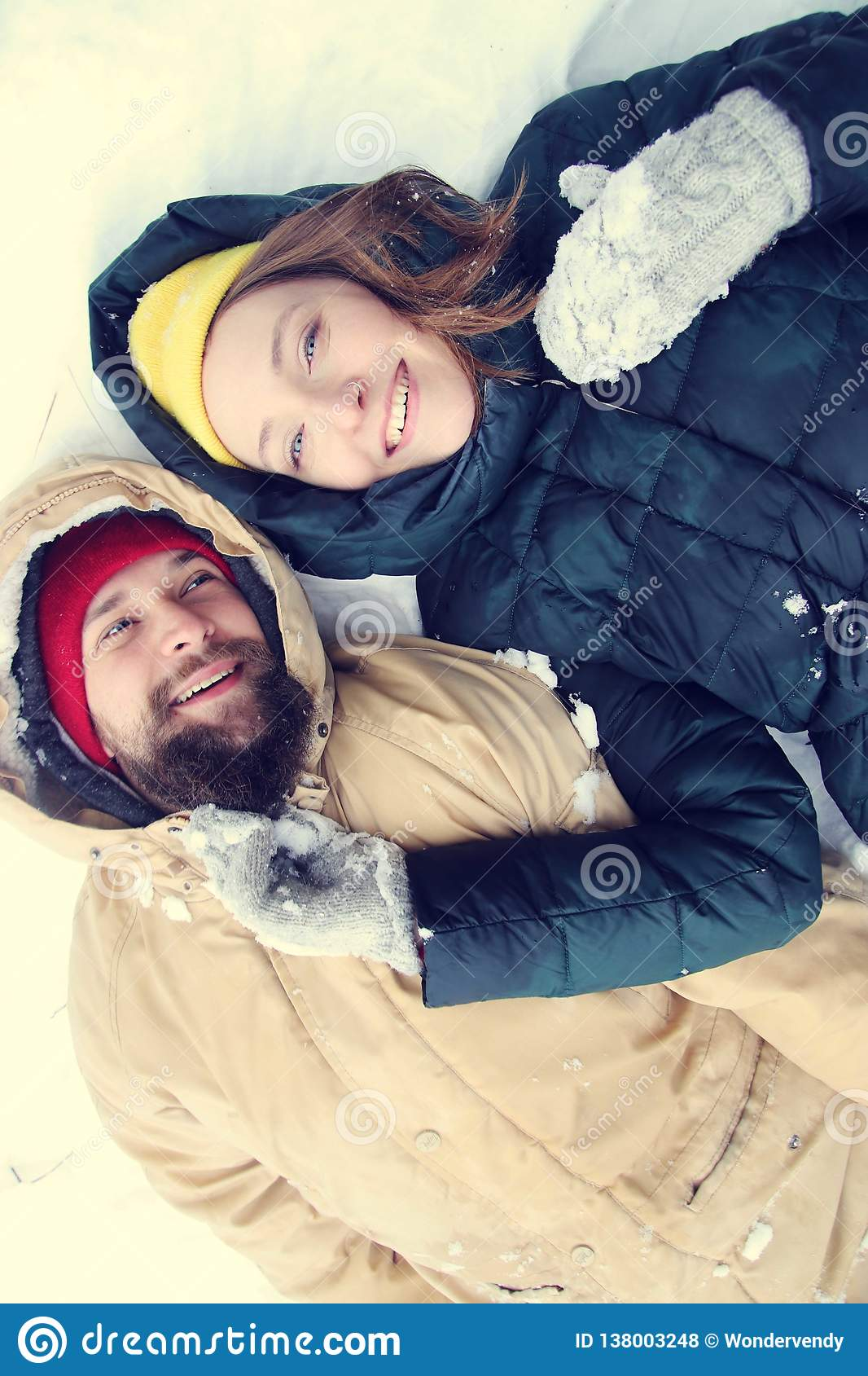 Happy couple in love having fun in the snow.