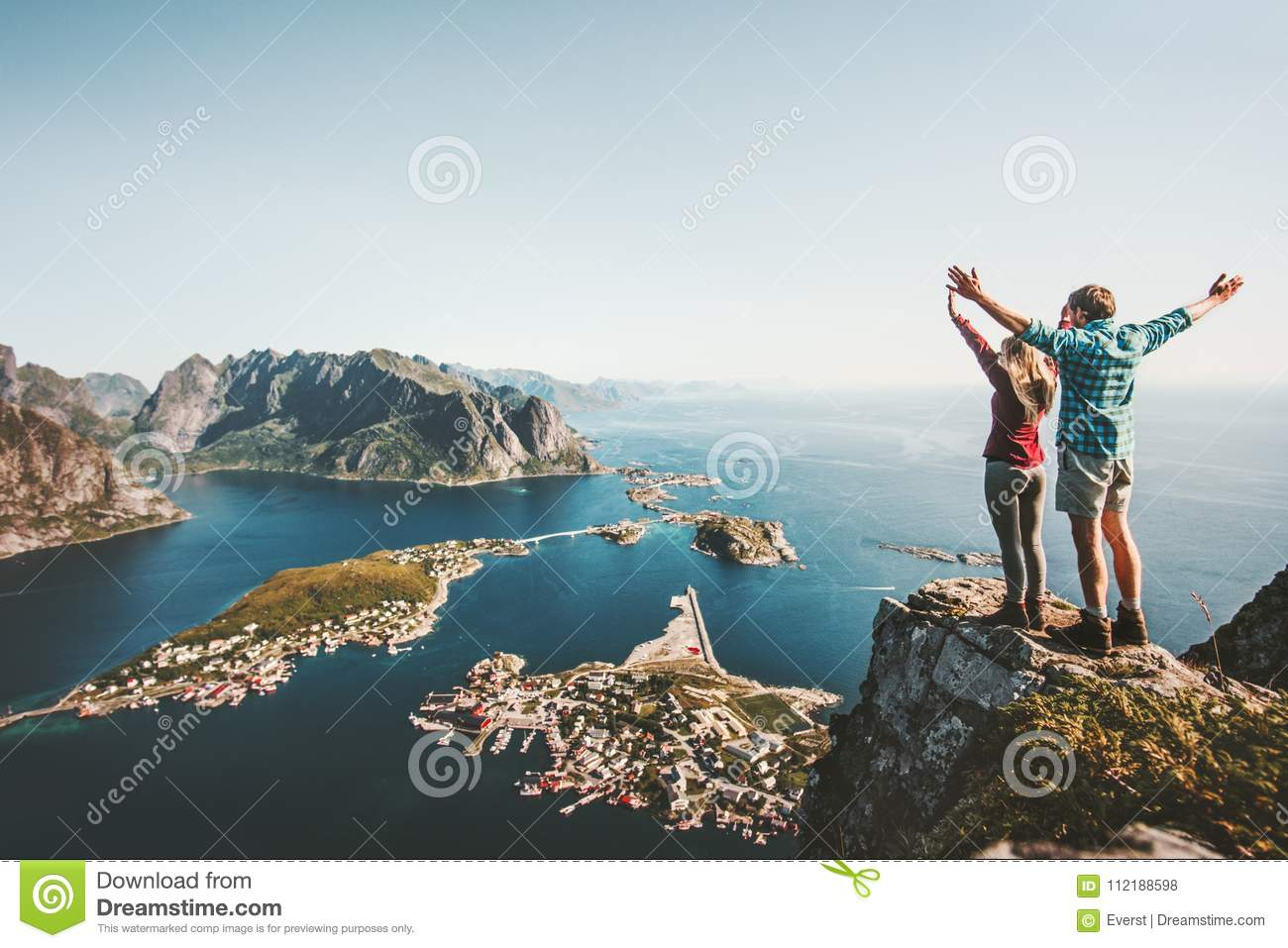 Happy Couple love and travel raised hands on cliff