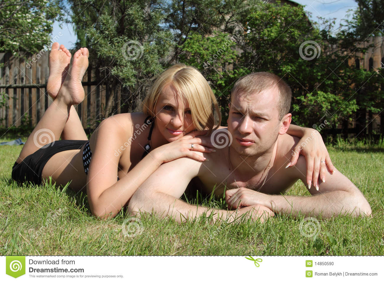 Happy couple is lying on green lawn.