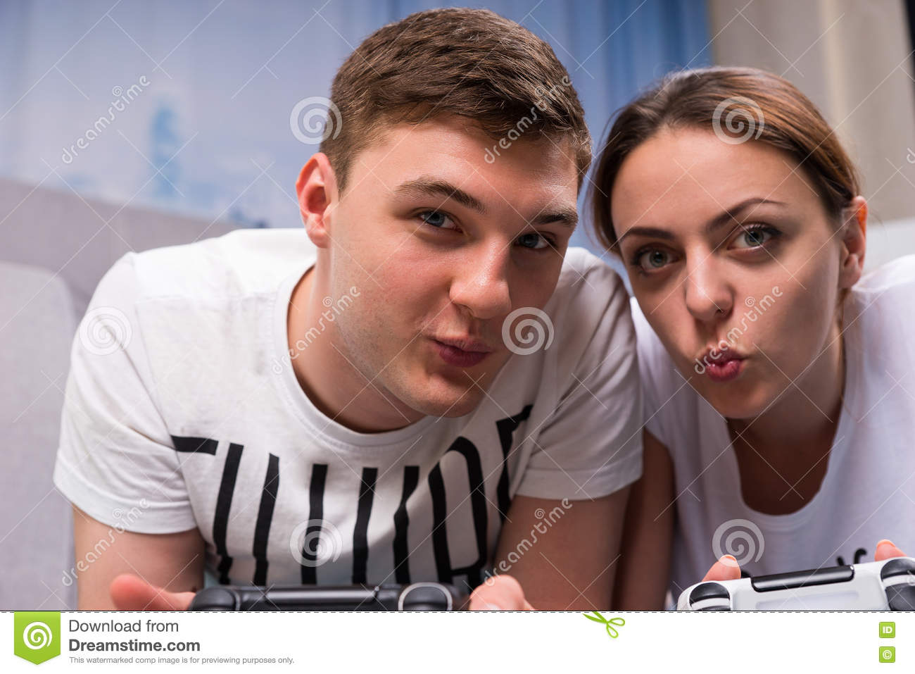 Happy couple lying on a rug and playing video games