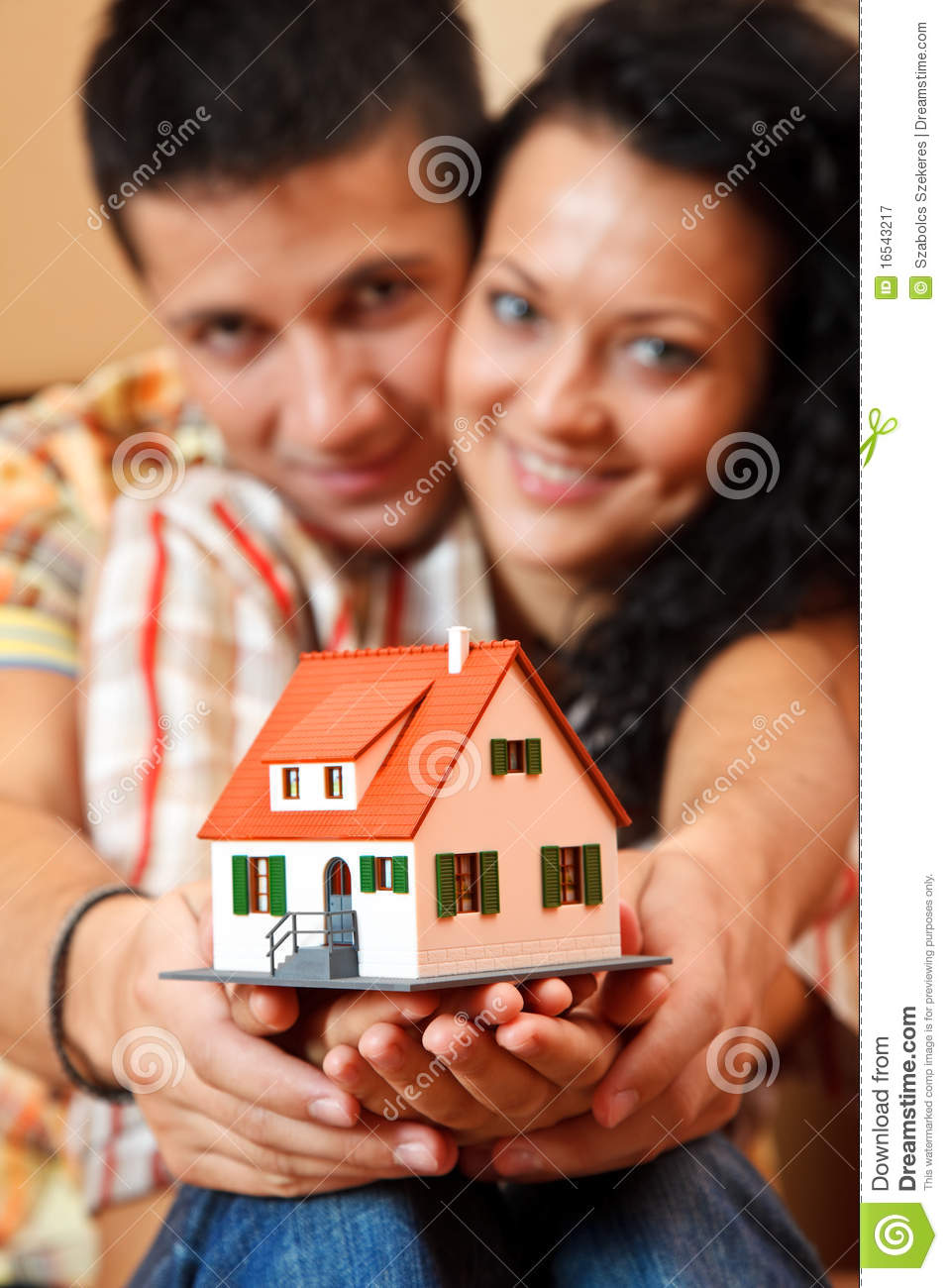 Happy couple with miniature house