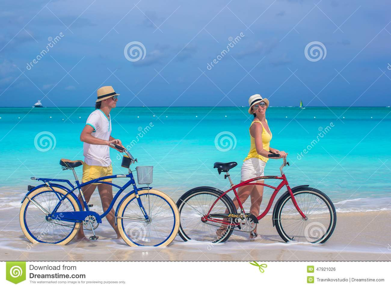 Happy couple riding bikes during tropical vacation stock for Tropical vacations for couples