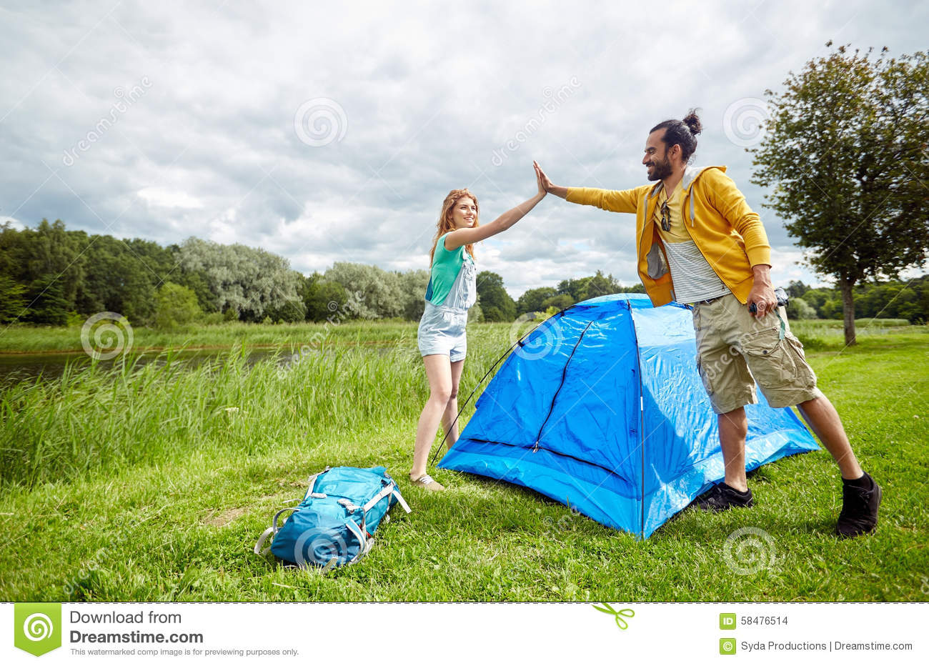 Happy couple setting up tent outdoors & Happy Couple Setting Up Tent Outdoors Stock Photo - Image of ...
