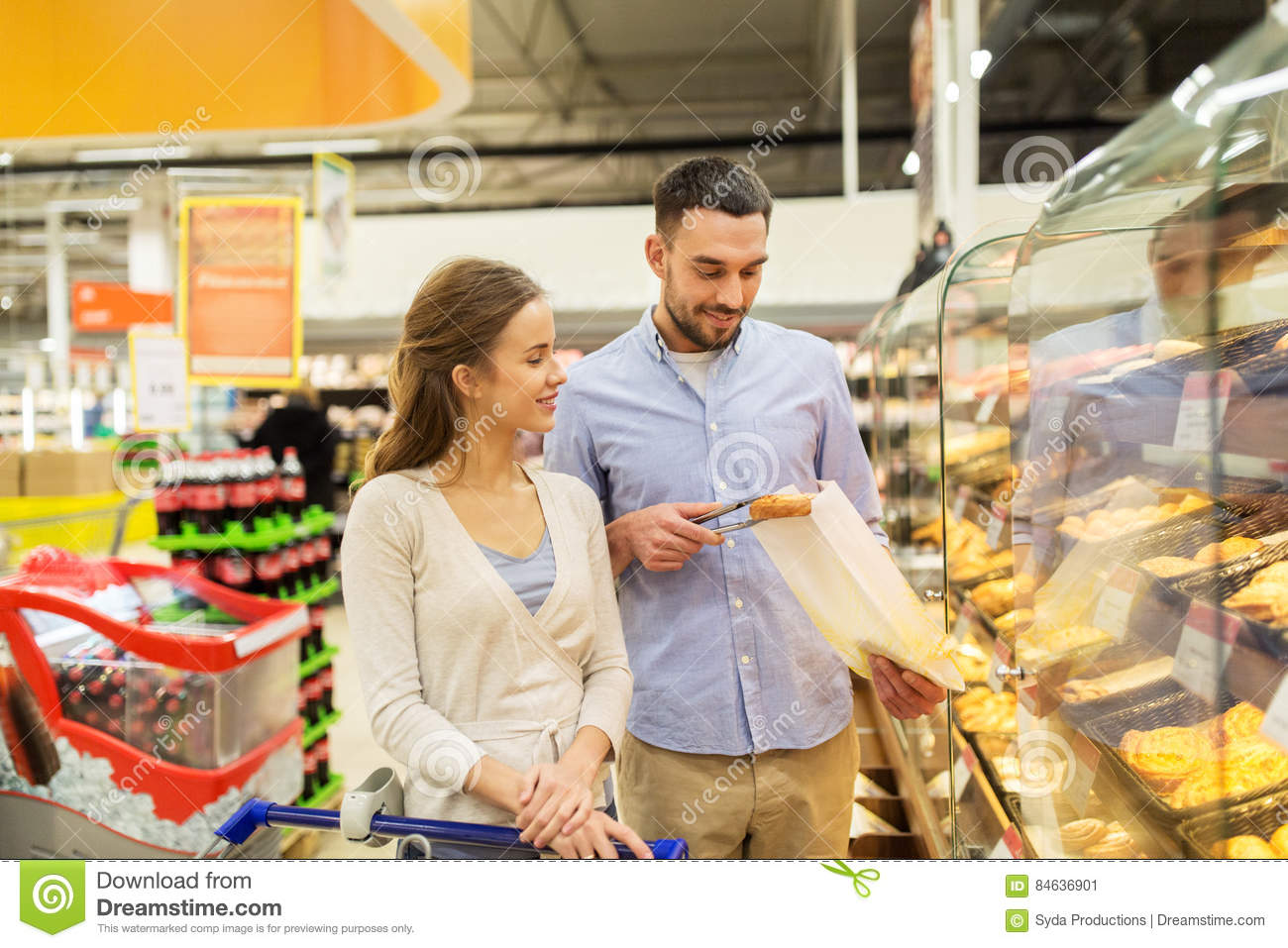 Happy Couple With Shopping Cart At Grocery Store Stock Image