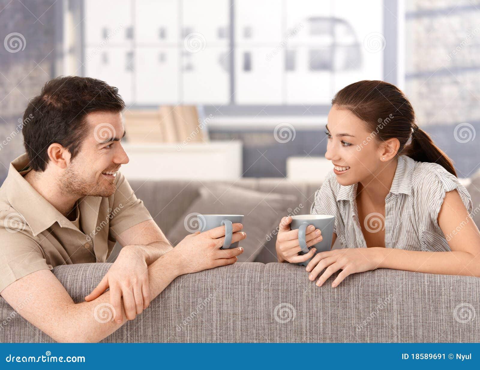 Happy Couple Sitting On Sofa Drinking Tea Smiling Stock