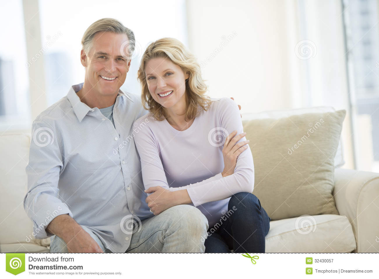 Happy Couple Sitting On Sofa In Living Room Royalty Free