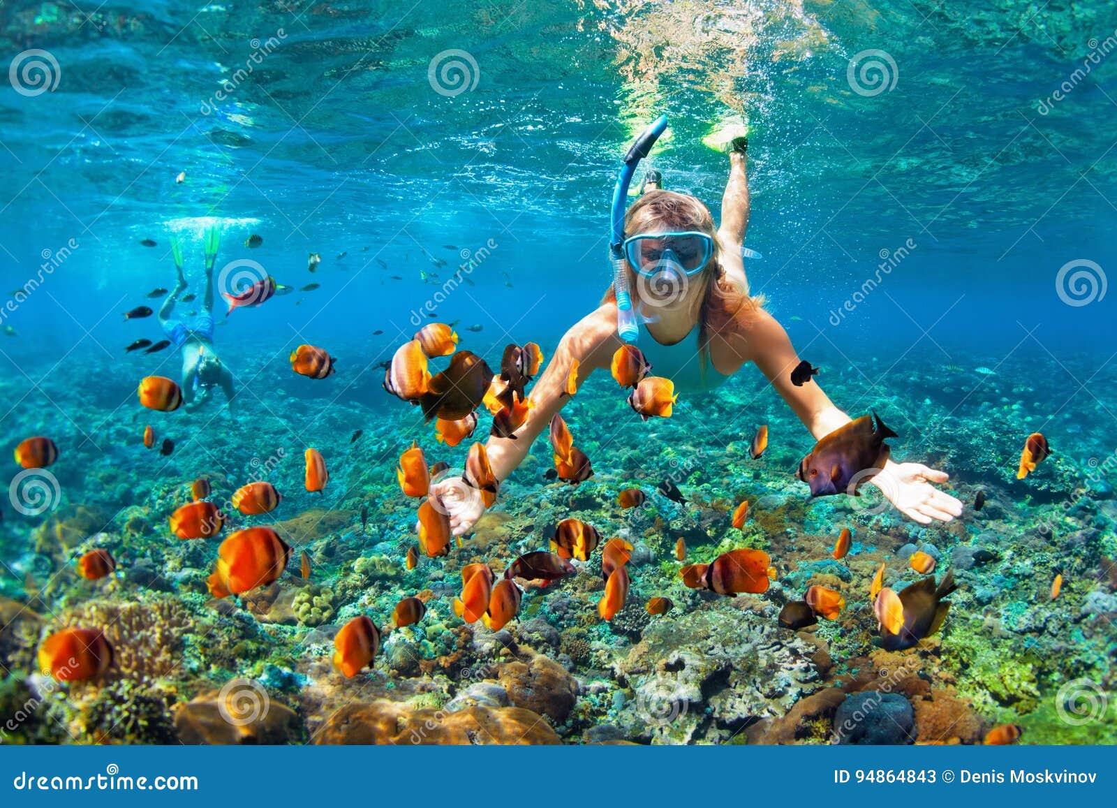 Happy couple snorkeling underwater over coral reef