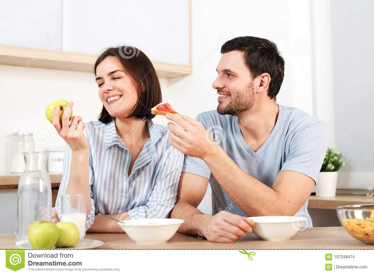Happy couple spend free time or weekend together at kitchen, glad husband suggests wife to eat snack, she refuses as