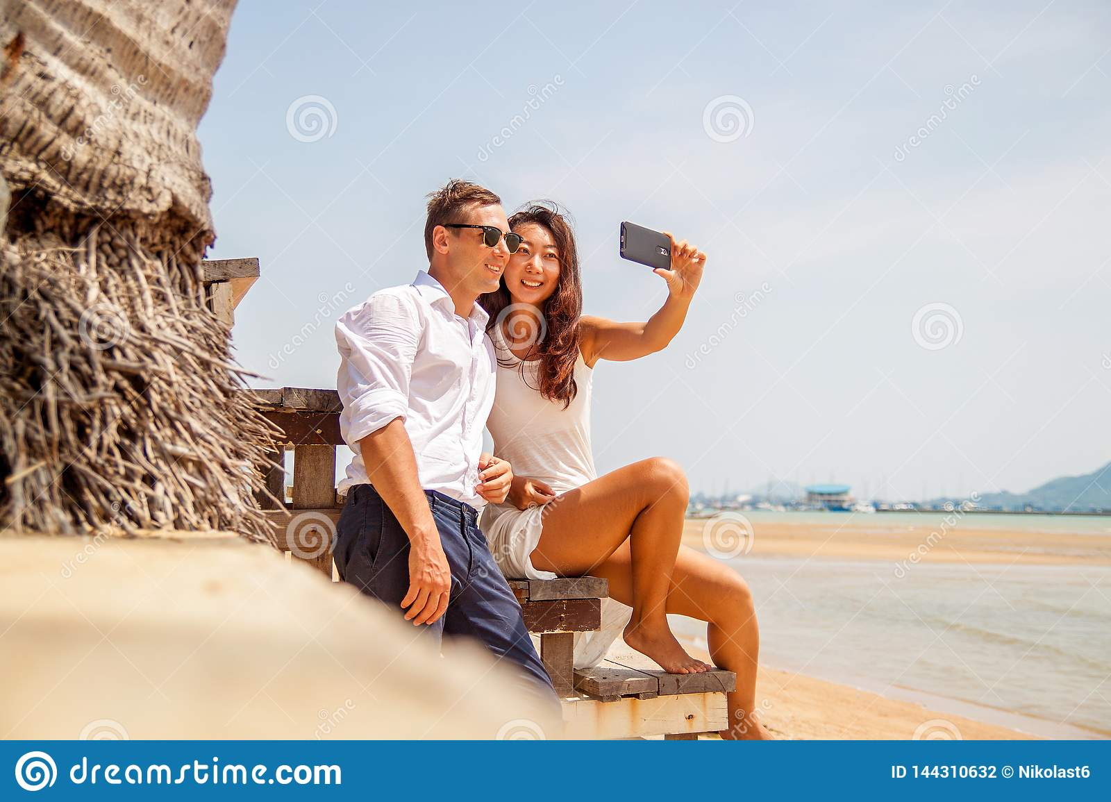 Happy couple taking a photo on white beach on honeymoon holiday.