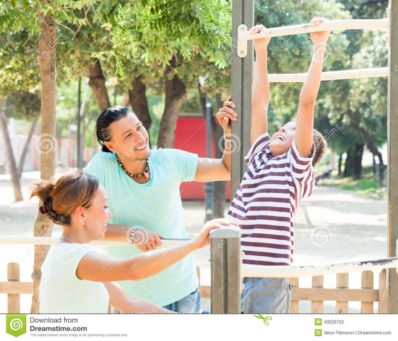 happy couple with teenage son training on pull up bar stock photo