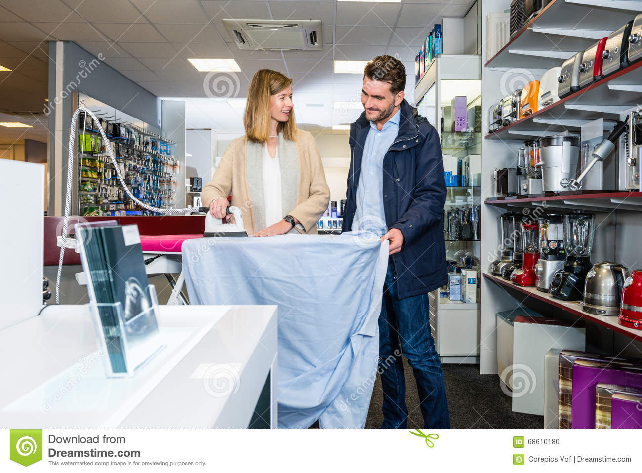 Happy Couple Testing Iron By Ironing Shirt In Hypermarket