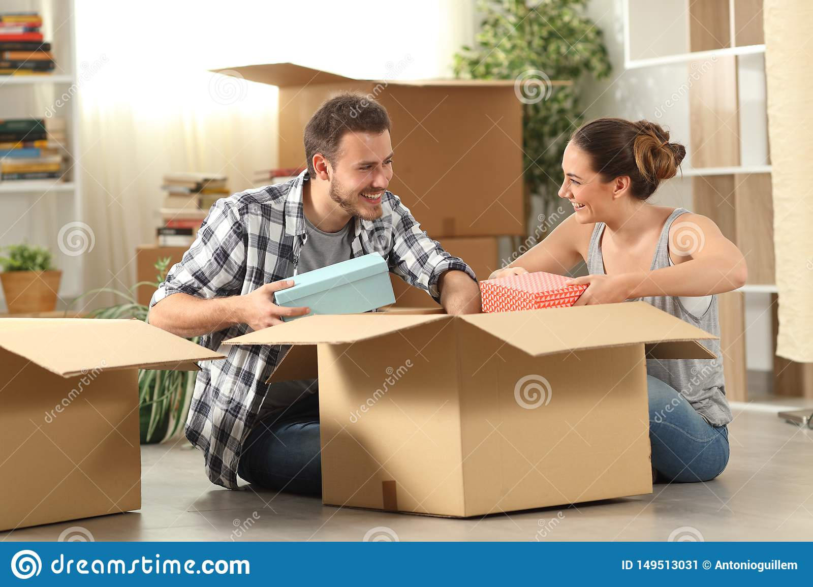 Happy couple unboxing belongings moving house