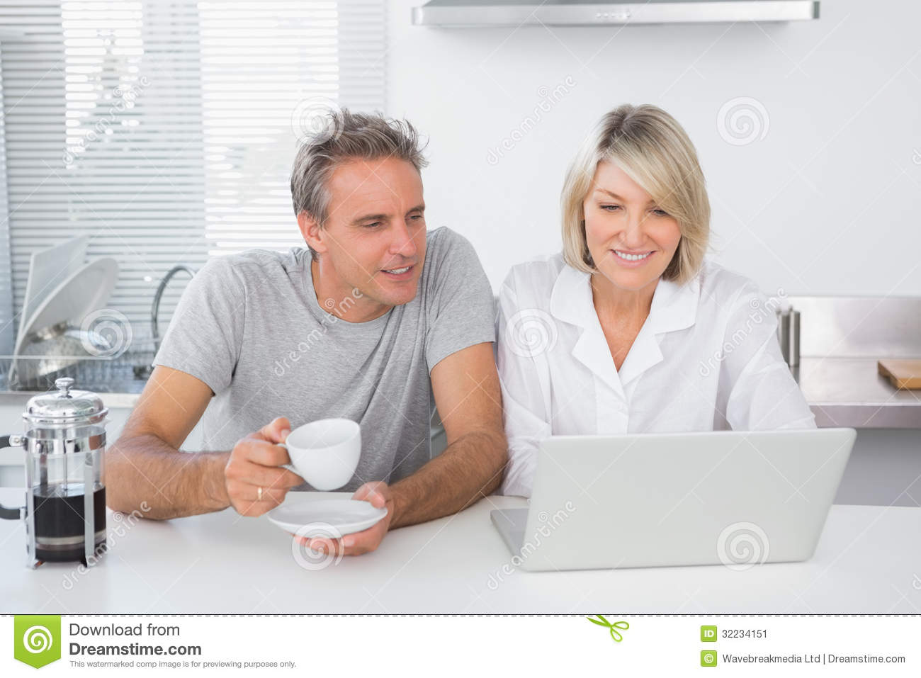 Happy couple using laptop in the morning