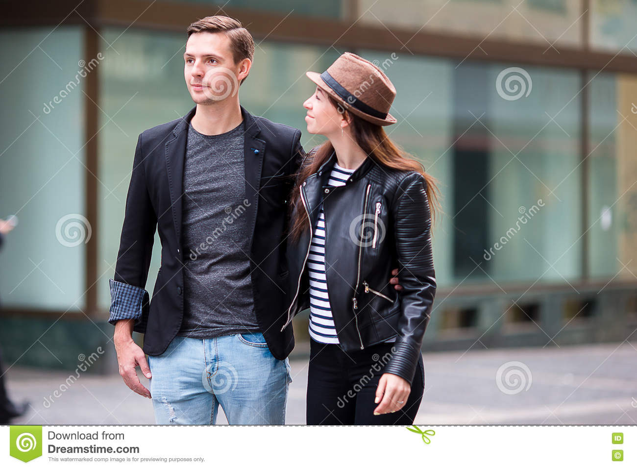 Happy couple walking in Europe. Smiling lovers enjoying cityscape with famous landmarks.
