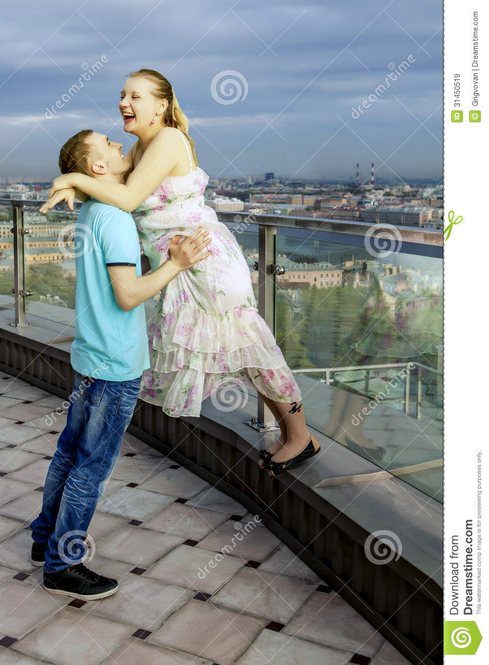 Happy Couple Walking On The Roof Of A High Building With Views Of The Big