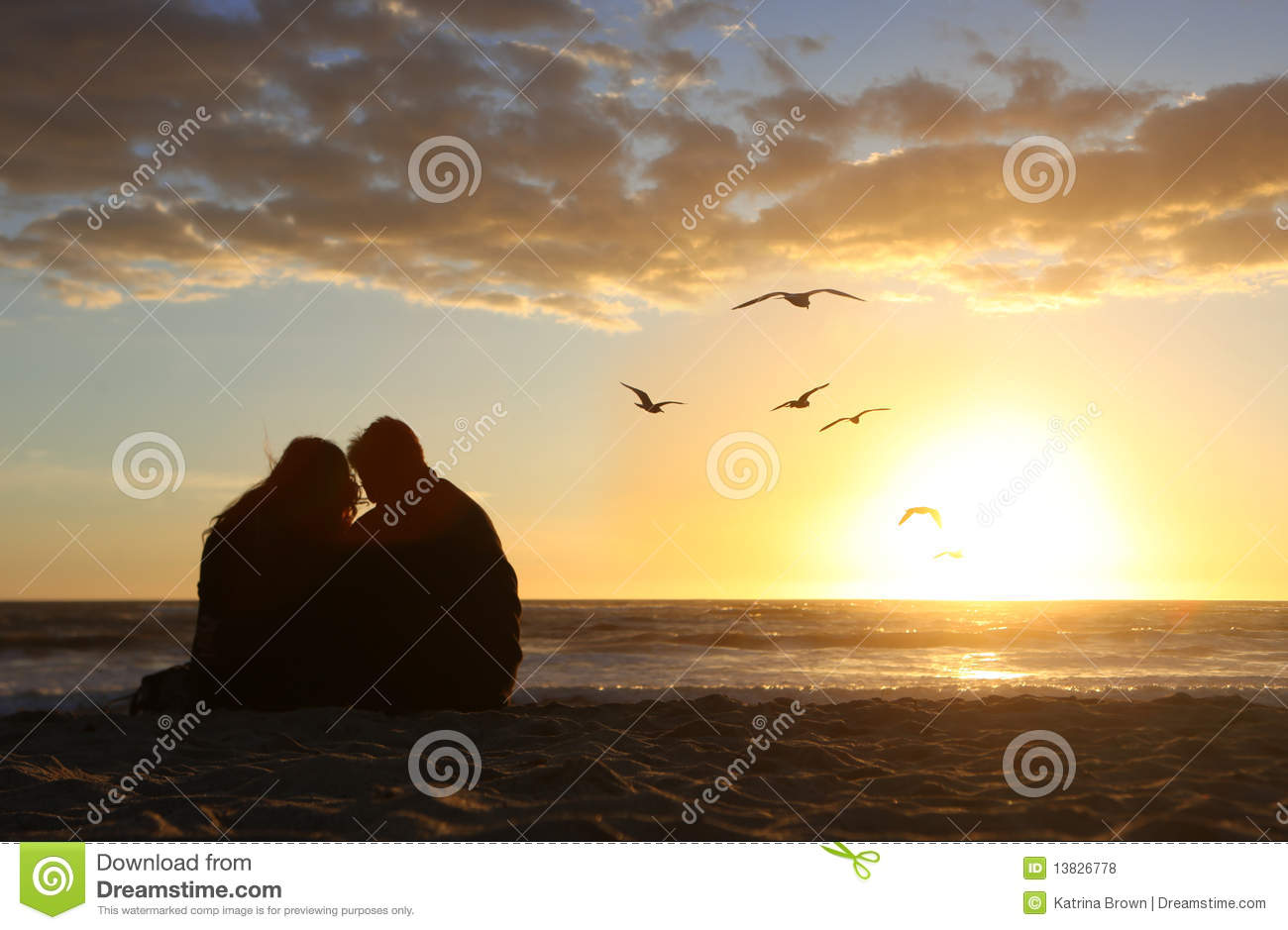 Happy Couple Watching the Sunset in Love on the Be