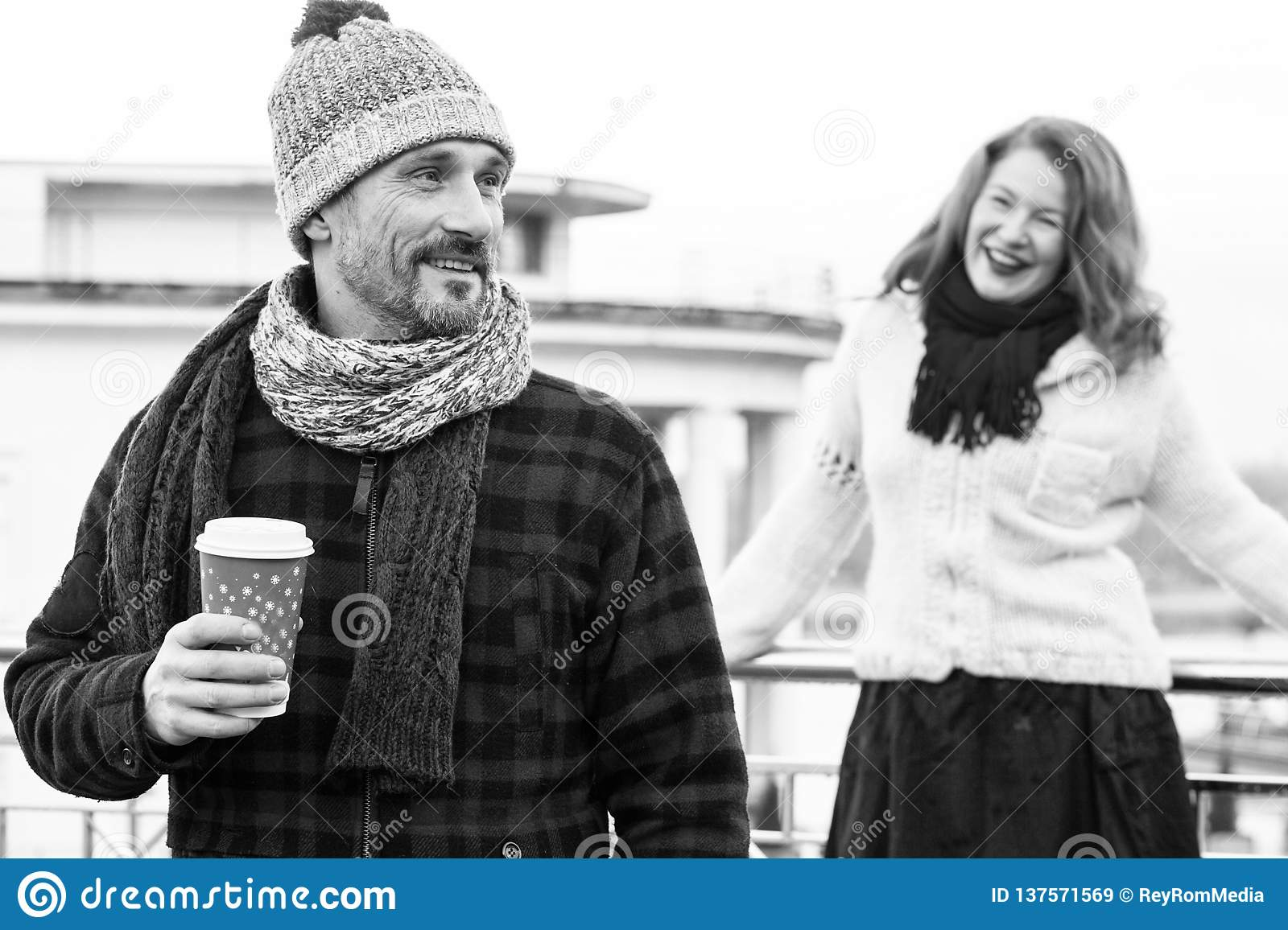 Happy couples loves drink coffee outdoor. Smiling guy holds craft cup with coffee and hiding it from girlfriend behind.