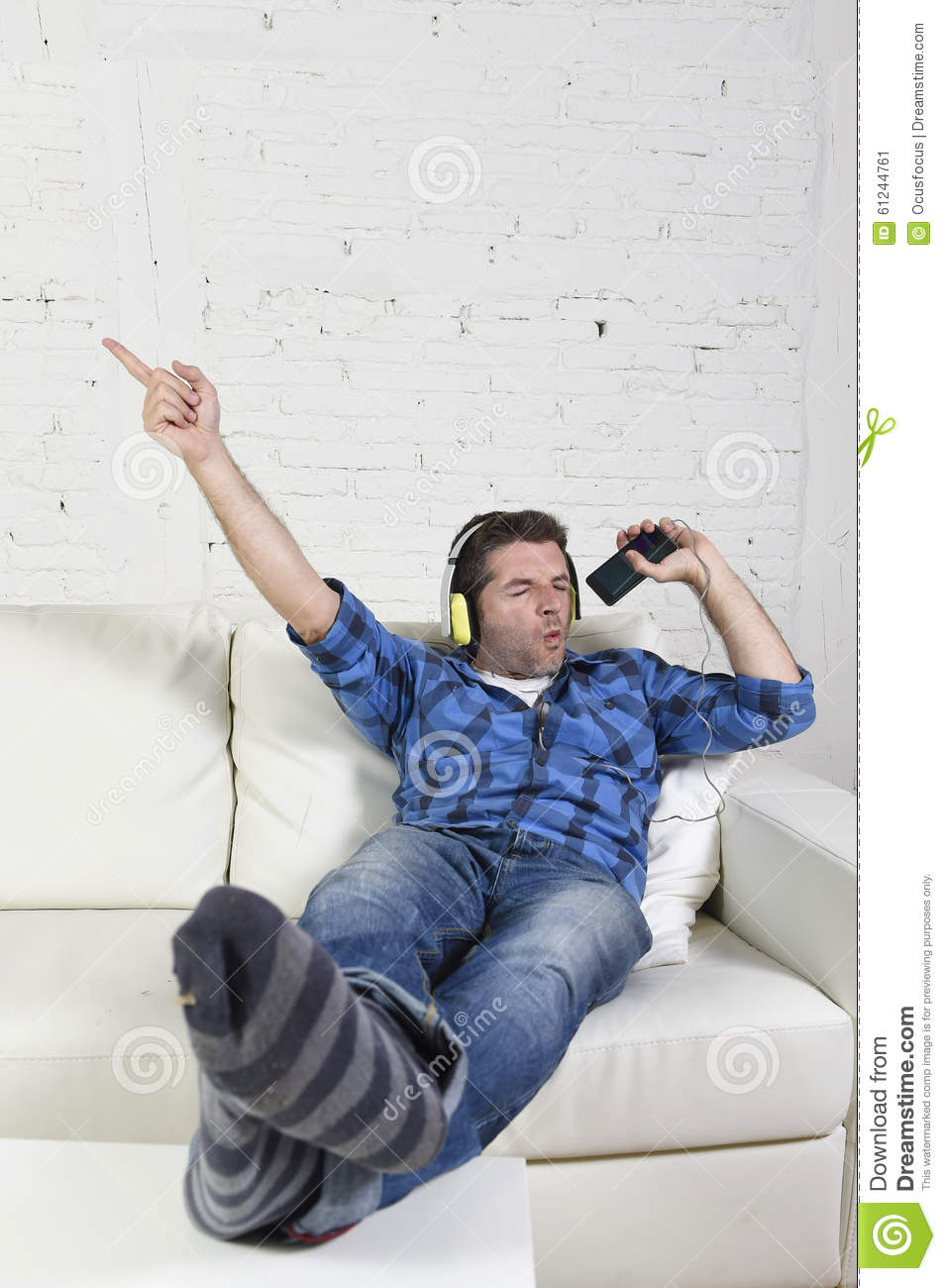 Download happy crazy man on couch listening to music holding mobile phone as microphone stock image
