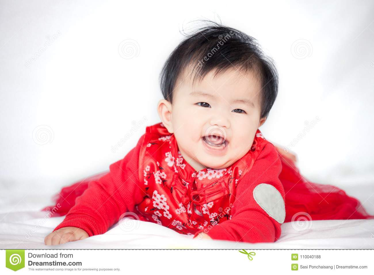 e55923a84 Happy cute asian baby girl in chinese tradition dress smiling and crawling  in the bed