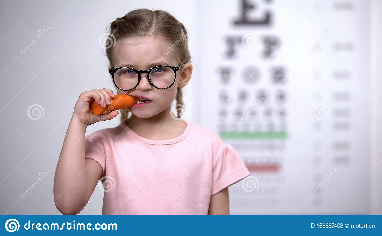 Happy cute girl in eyeglasses eating carrot, vitamin A for good vision, health