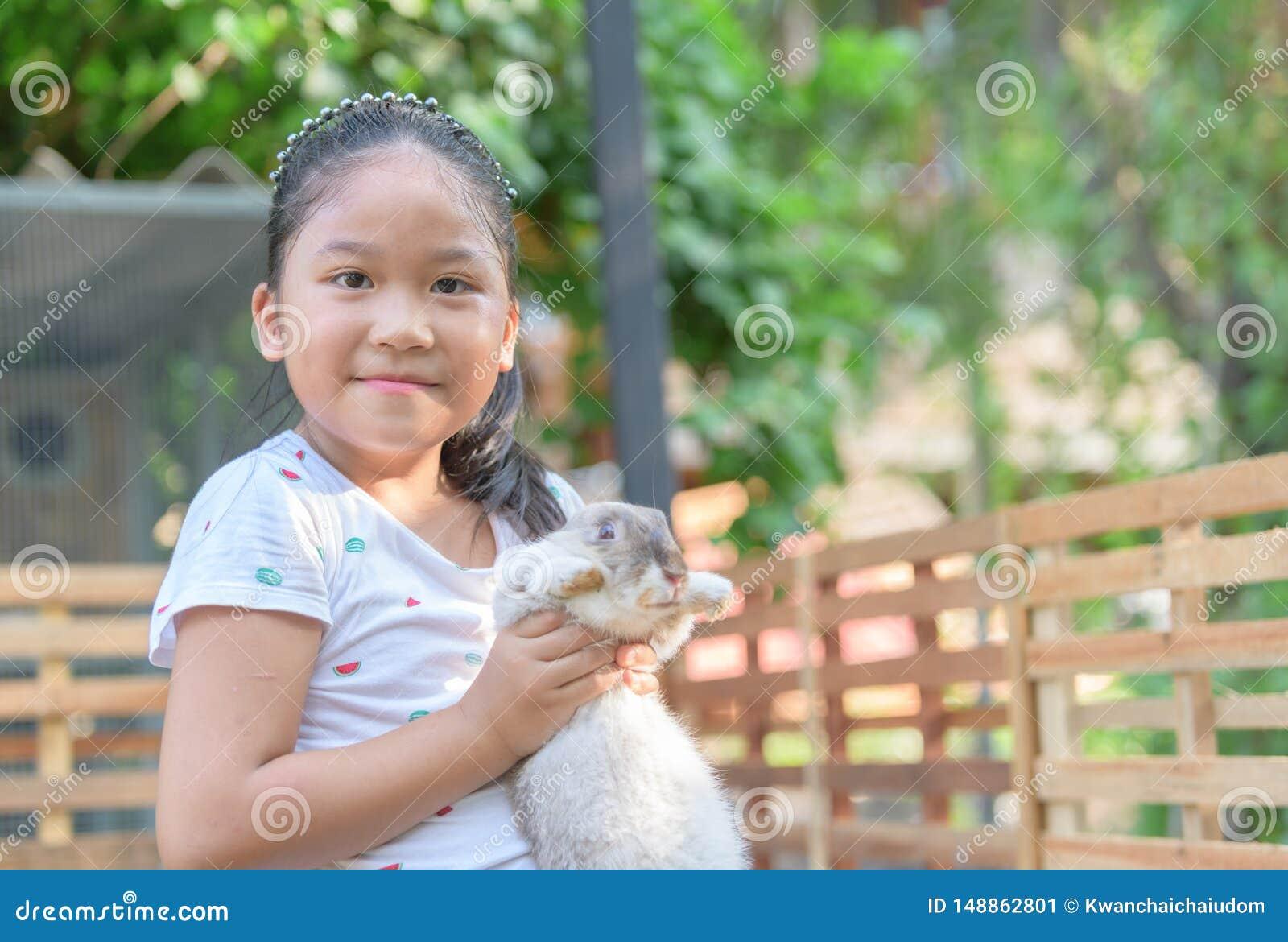 Happy cute girl hug rabbit in farm