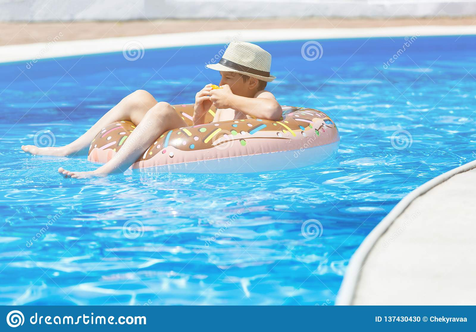 Happy cute little boy teenager lying on inflatable donut ring with orange in swimming pool. Active games on water, vacation