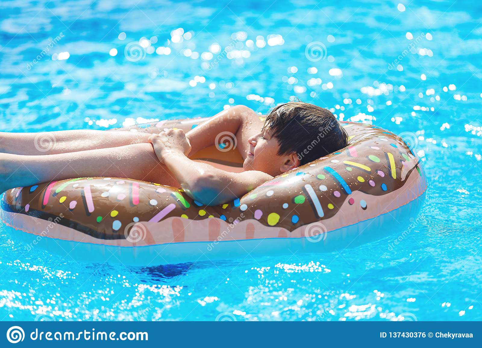 Happy cute little boy teenager lying on an inflatable donut ring in swimming pool. Active games on water, vacation, holidays