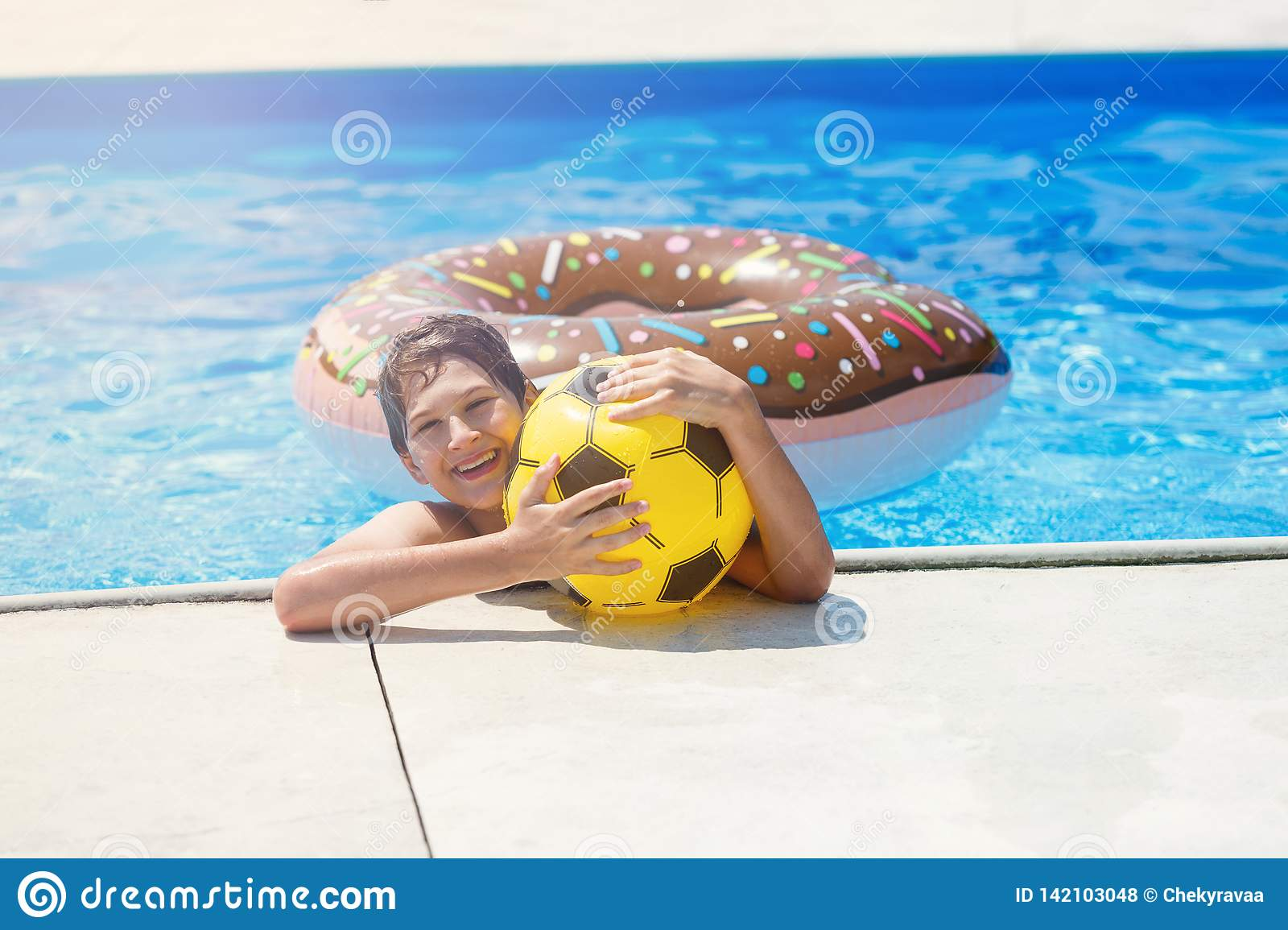 Happy cute little boy teenager in swimming pool. Active games on water, vacation, holidays concept. Chocolate donut.