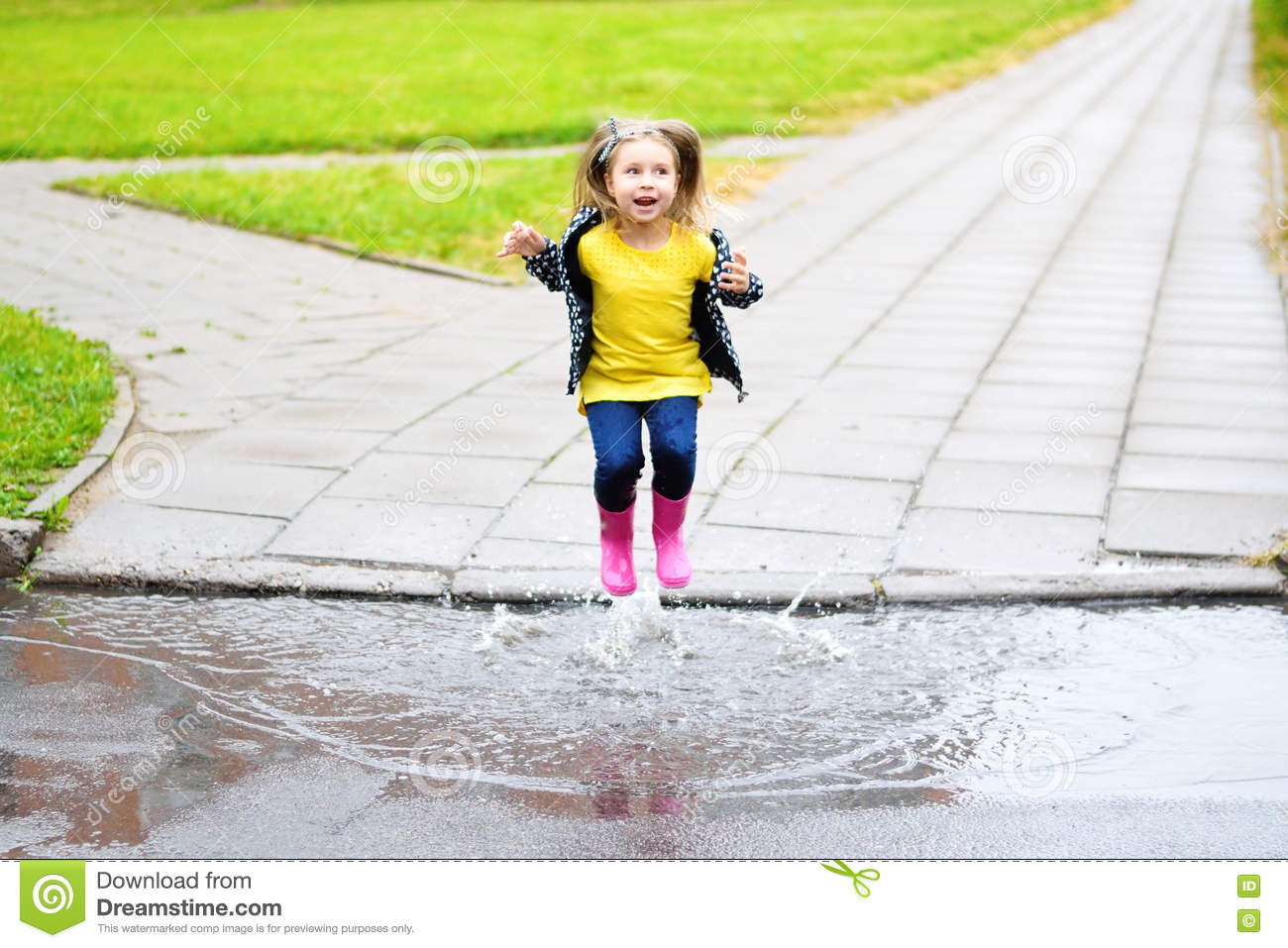 a personal belief of jumping into puddles A pair of red rubber boots are jumping into a big puddle feet in rubber boots rain puddle city close up little girls feet in red gumboots with daisies in them standing in green grass.