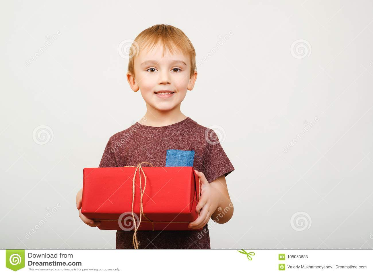 Happy cute little kid holding red gift box isolated over white background.