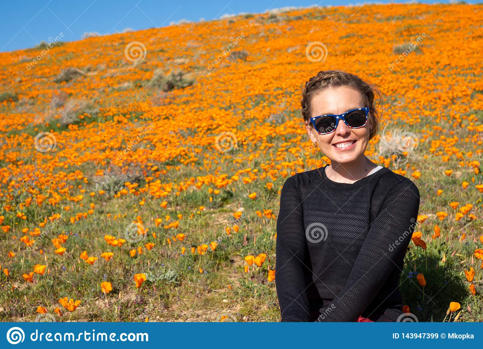 Happy, cute young adult woman posing at the poppy reserve in California during the superbloom