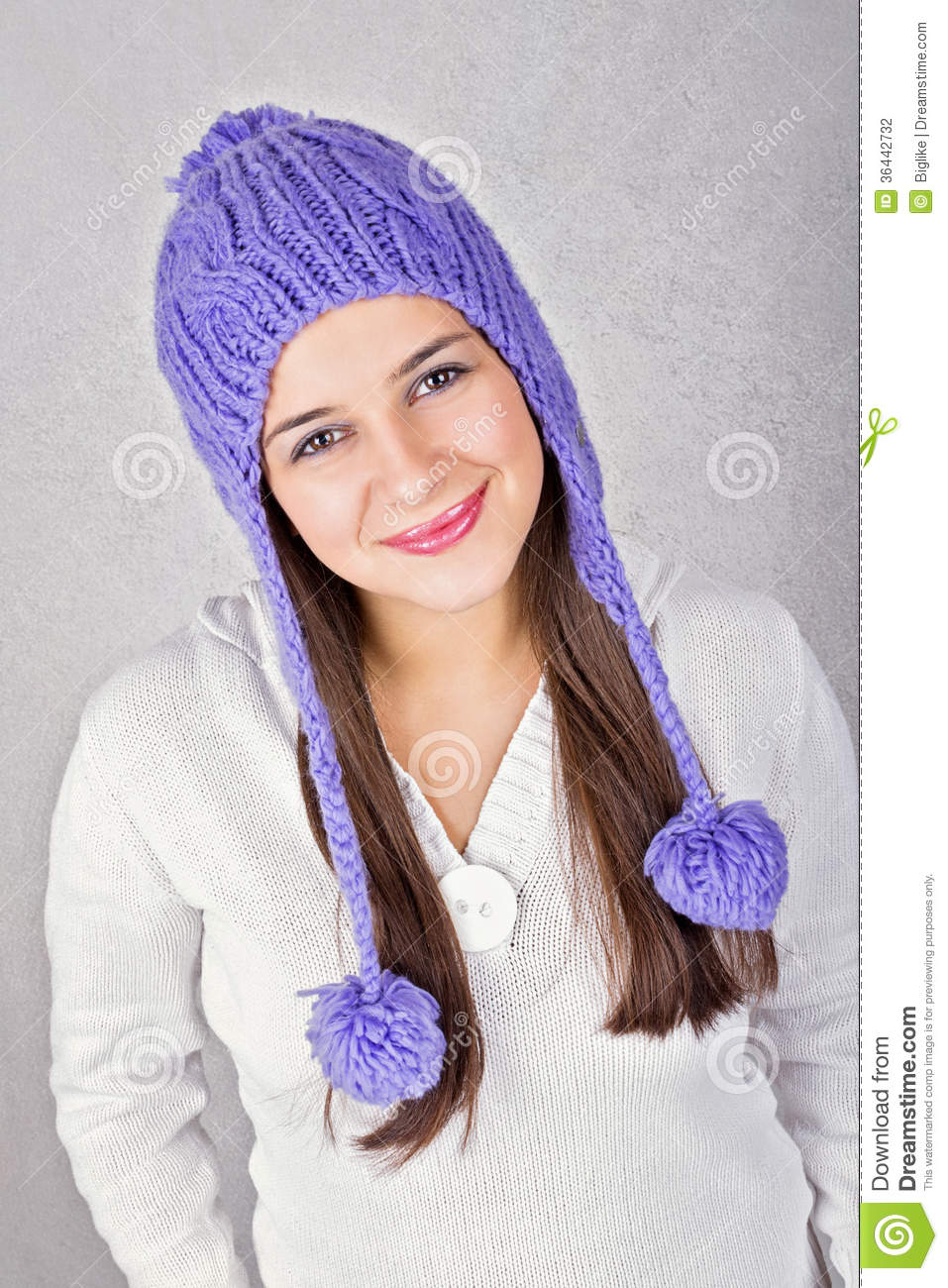 Happy cute Caucasian brunette young teenage girl wearing purple beanie hat  and white sweater smiling looking at camera against gray texture background. 84edd4e3f53