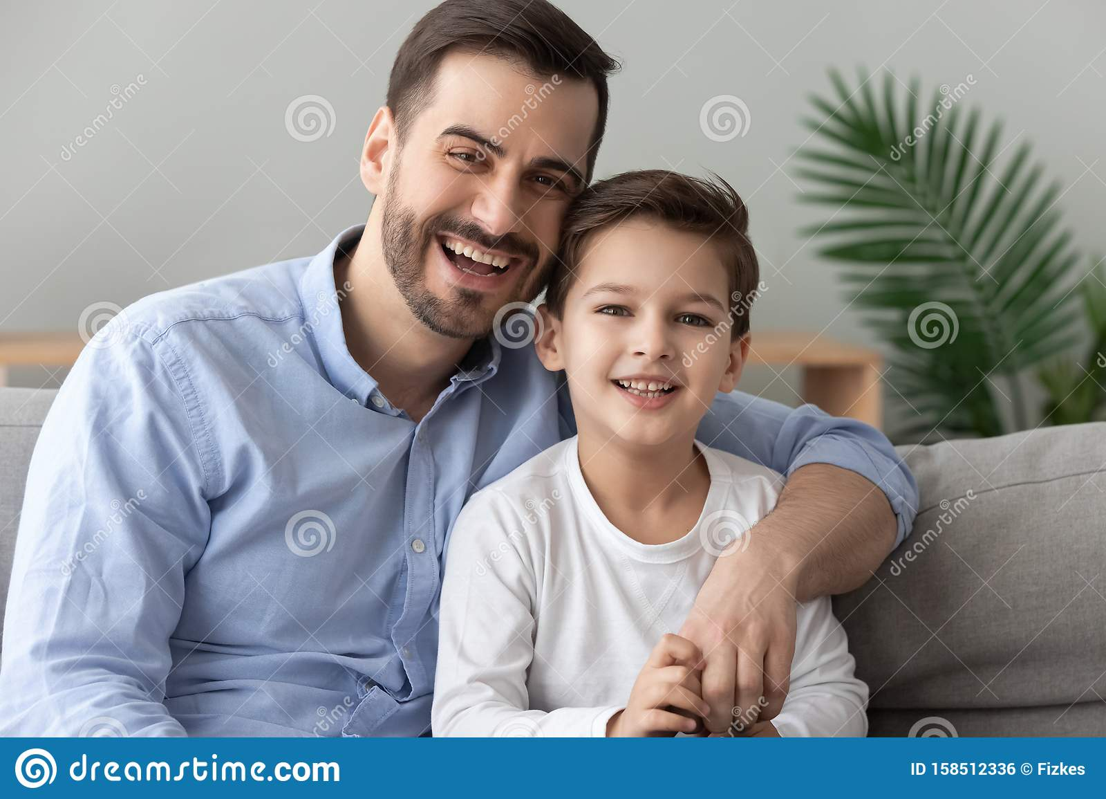 Happy Dad Embracing Son Looking At Camera Sit On Sofa Stock Photo