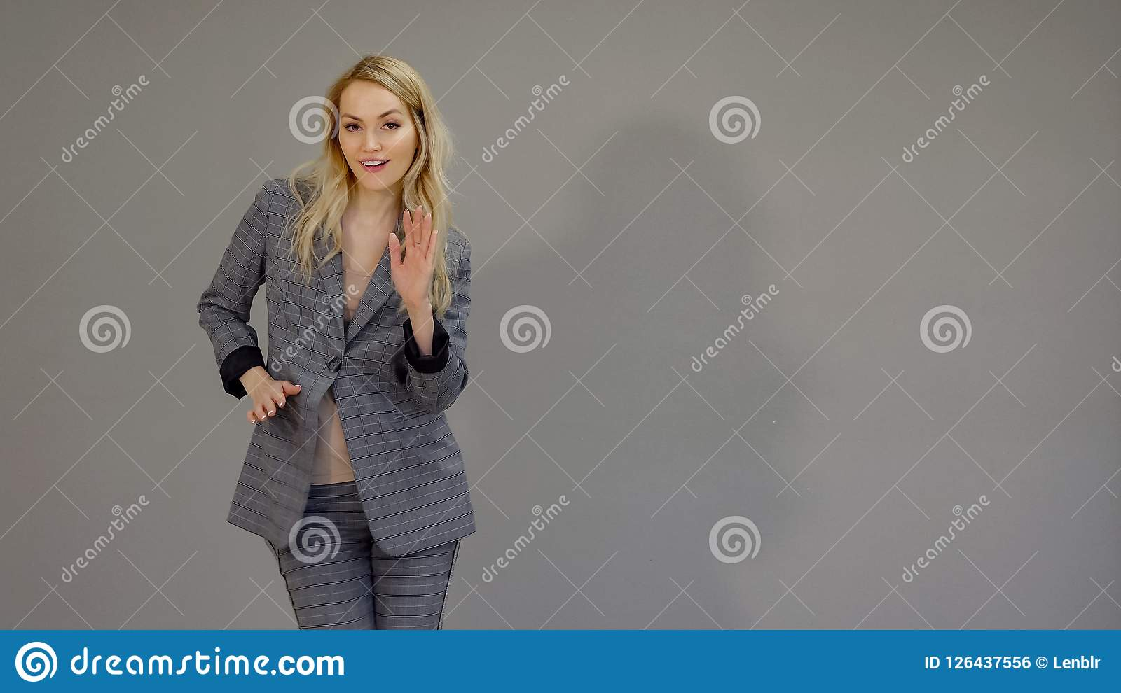 Happy dancer girl in suit dancing freestyle in office on the grey background.