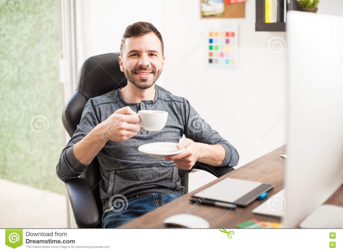 Coffee At Work ~ Happy designer drinking coffee at work stock photo image