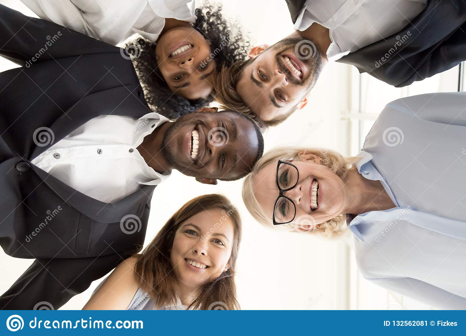 Happy diverse business team gathering in circle looking at camer