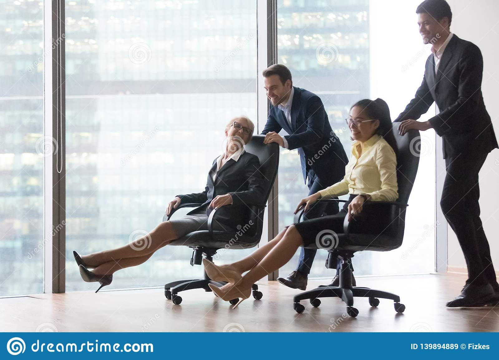 Happy diverse employees having fun riding on chairs in office