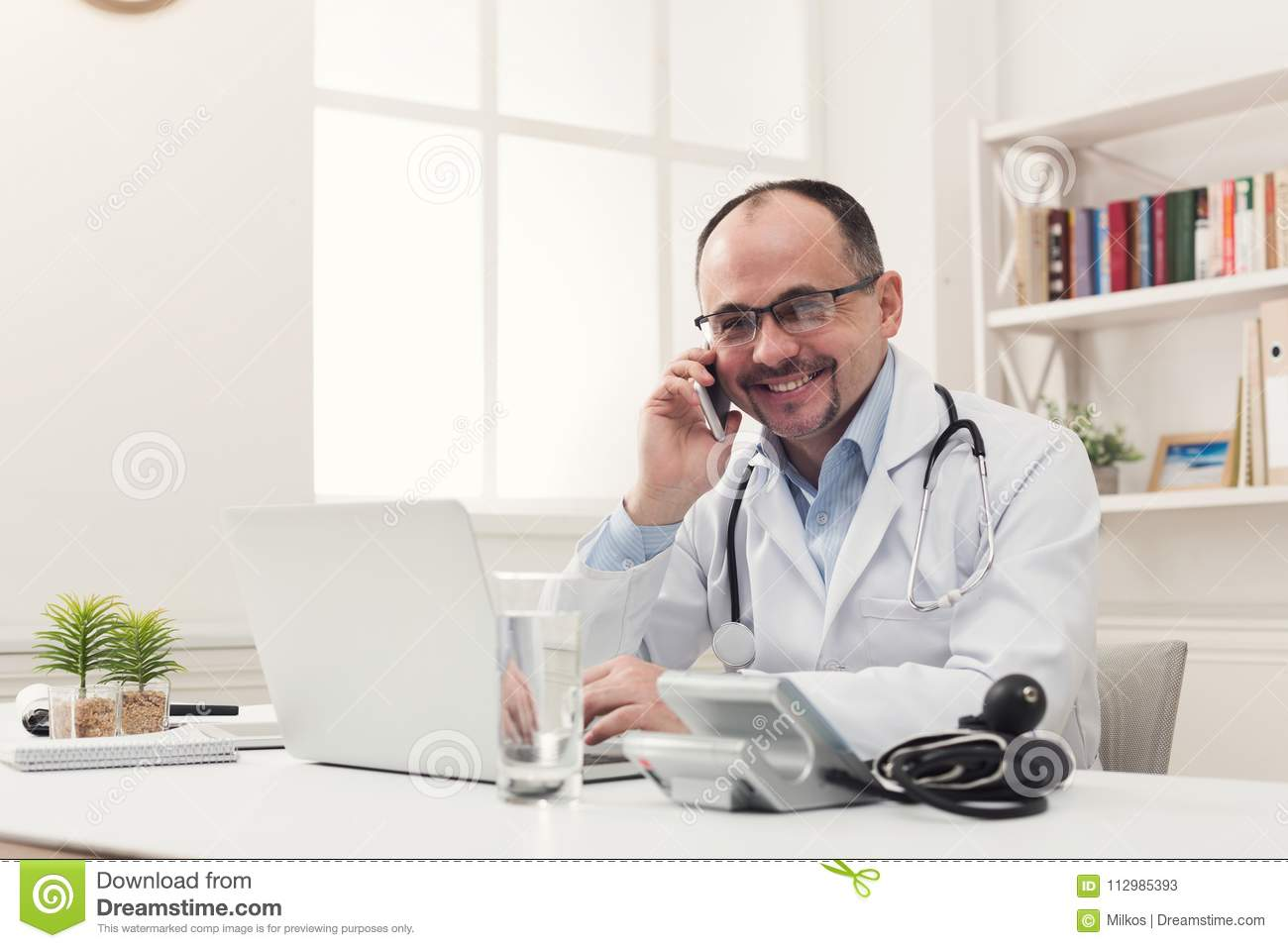 Happy doctor talking on phone with his patient