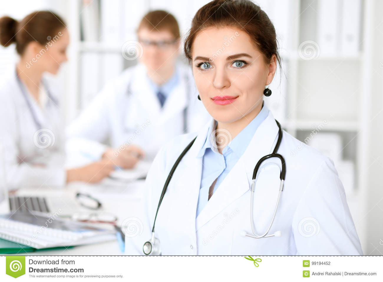 Happy doctor woman with medical staff at the hospital sitting at the table