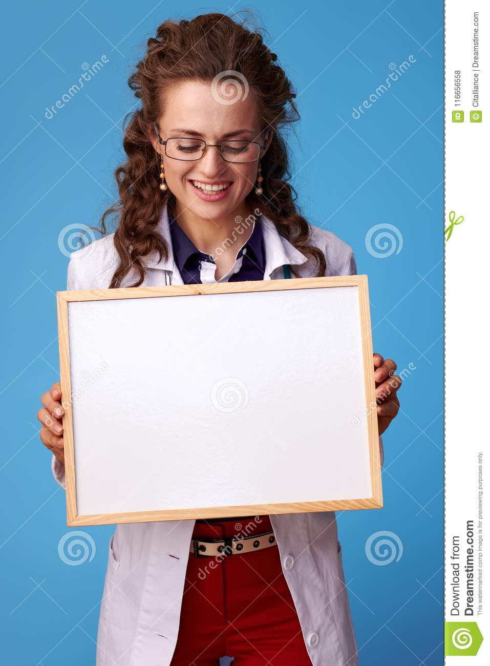 Happy doctor woman looking at blank board on blue